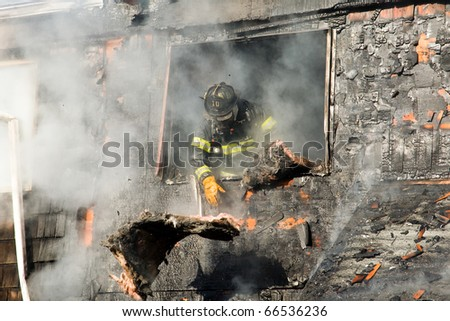 Firefighter operating at a house fire. - stock photo
