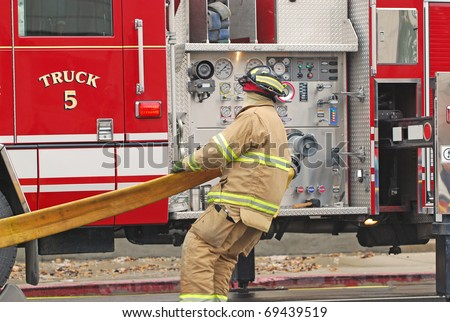 Firefighter pulling on a hose in front of a firetruck. - stock photo