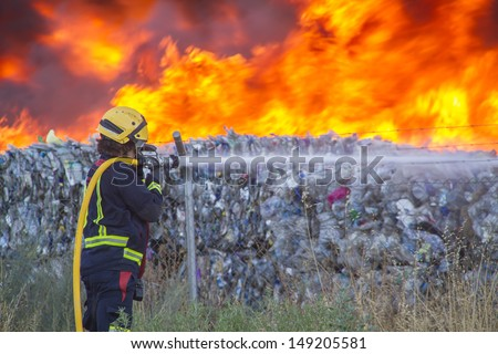firefighter putting out a fire with water hose