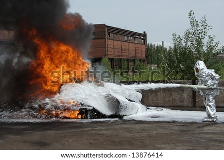 firefighter  quenches burning tires - stock photo