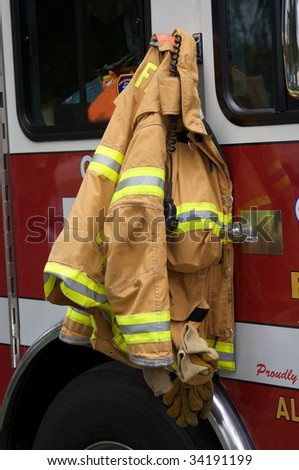 Firefighter's jacket hanging on fire truck - stock photo