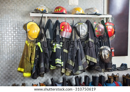 Firefighter's uniforms and gear arranged at fire station - stock photo