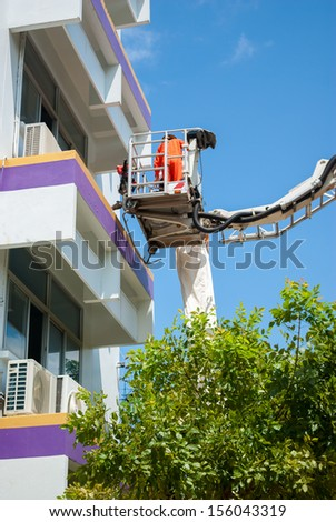 Firefighter serving with the fire truck ladder extended - stock photo
