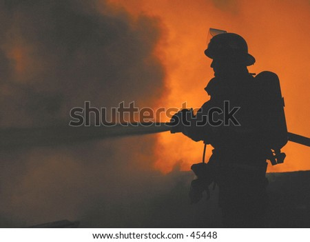 firefighter silhouetted at a fire - stock photo