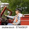 firefighter sitting in a vintage firetruck with his hand on the steering wheel - stock photo