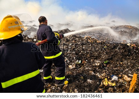 Firefighter spraying water on the burning pile of garbage. - stock photo