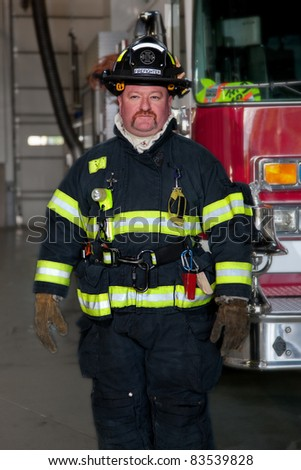 FireFighter standing in front fire truck portrait - stock photo