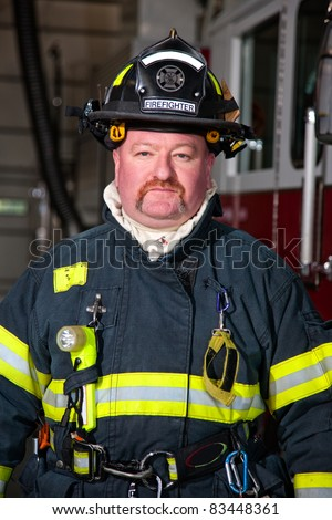 Firefighter standing in front of a fire truck - stock photo
