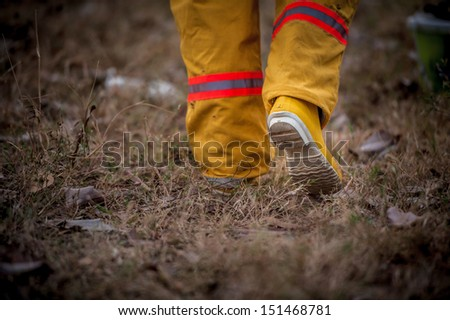 firefighter suit walking on grass  - stock photo