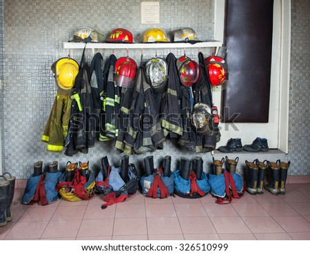 Firefighter suits and gear arranged at fire station - stock photo