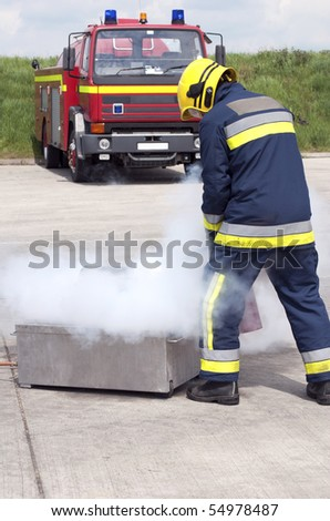 Firefighter using extinguisher - stock photo