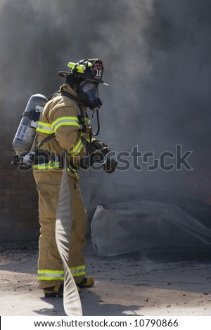 Firefighter waits for water - stock photo