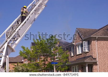 Firefighter wearing a self contained breathing apparatus on an engine ladder surveys an extinguished fire that damaged a roof top. - stock photo