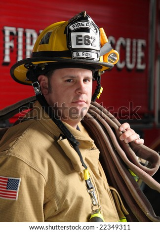 firefighter with hose and firetruck in background - stock photo