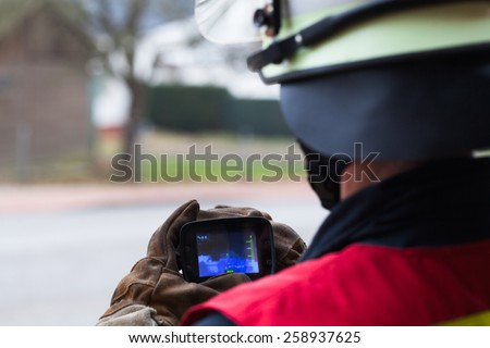 Firefighter with in action thermal camera - stock photo