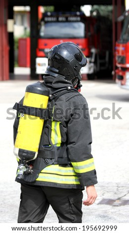 firefighter with yellow  oxygen cylinder and the helmet walks towards the fire - stock photo