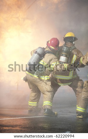 Firefighters attack a propane fire. - stock photo
