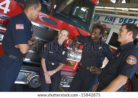 Firefighters chatting by a fire engine - stock photo