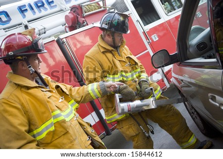 Firefighters cutting open a car to help an injured person - stock photo