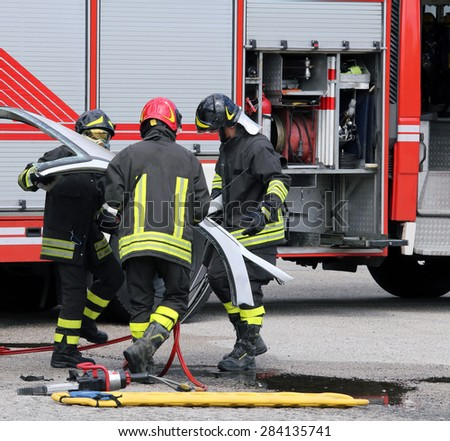firefighters during a road accident with car parts and the firetruck