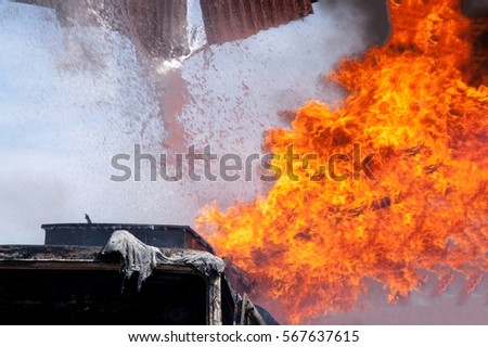 Firefighters extinguish a building and truck