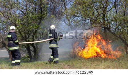 Firefighters extinguish a fire in a forest fire by water flooding - stock photo