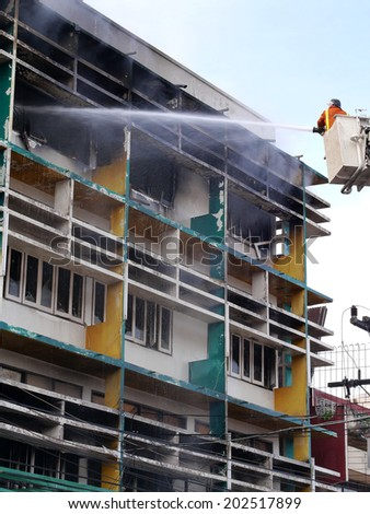 Firefighters extinguished the fire in the building. Firemen on a crane against wall of fire - stock photo