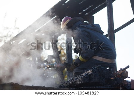 Firefighters extinguishing fire in building - stock photo