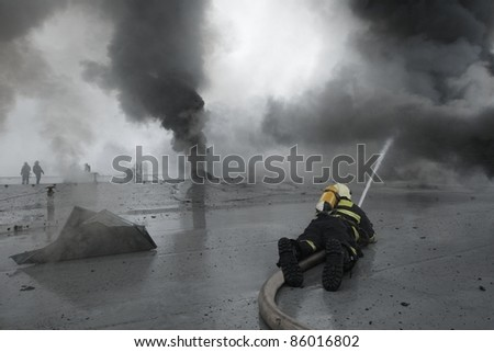Firefighters extinguishing the fire on the roof of a large building. - stock photo