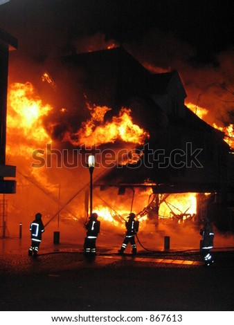 Firefighters fighting a burning building (some noise) - stock photo