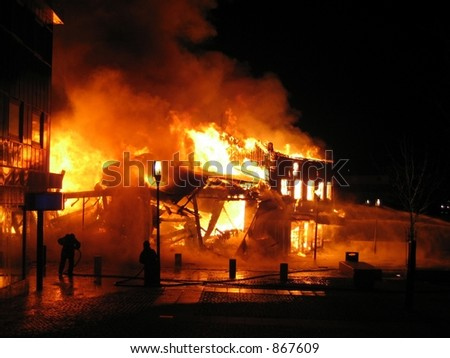 Firefighters fighting a flaming inferno (some noise) - stock photo