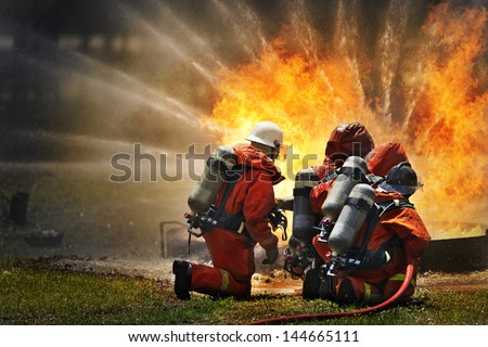 Firefighters fighting fire during training - stock photo