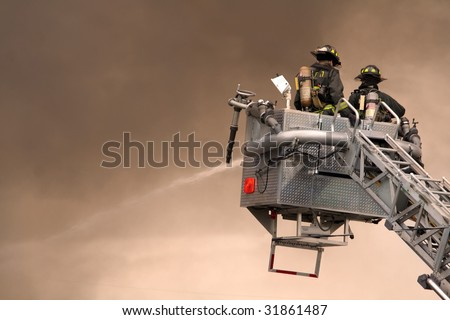Firefighters fighting fire from bucket atop a fire truck. - stock photo
