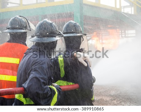 Firefighters fighting fire with pressured water during training exercise. Fire fighter spraying a straight steam into fire off. - stock photo