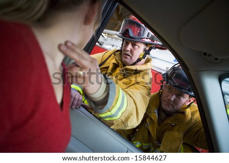 Firefighters helping an injured woman in a car - stock photo