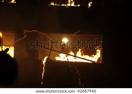 Firefighters in a window of a burning building. - stock photo