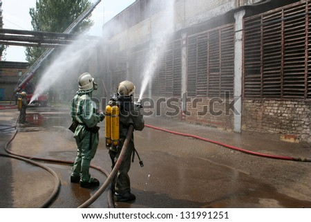 firefighters in chemical protection suits and gas masks were ready to fire - stock photo
