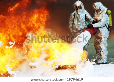 firefighters in protective suits extinguish a big fire - stock photo