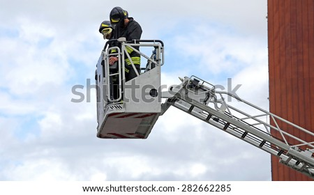 firefighters in the fire truck basket during the practice of training in fire station - stock photo