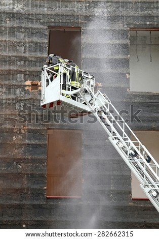 firefighters in the fire truck basket during the practice of training in firehouse - stock photo