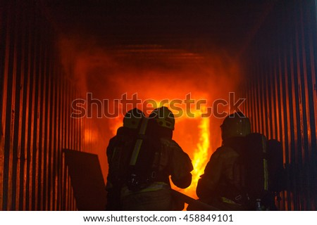 Firefighters kneeling in front of a blazing fire.