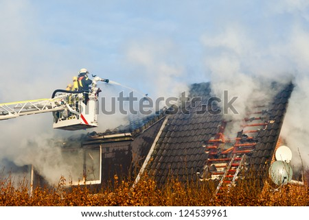 Firefighters on turntable ladder at house fire - stock photo