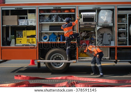 Firefighters prepare for the tools from the truck during a serious accident - stock photo