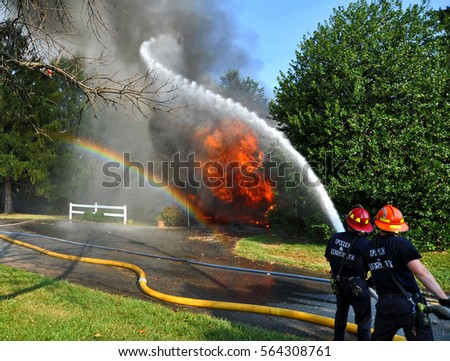 firefighters putting out residential fire as hose spray makes rainbow