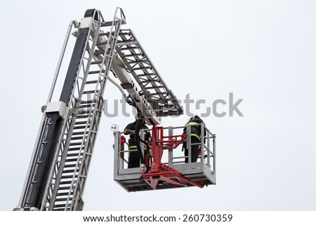 Firefighters rescuers at firetrack retractable ladder during accident fighting - stock photo