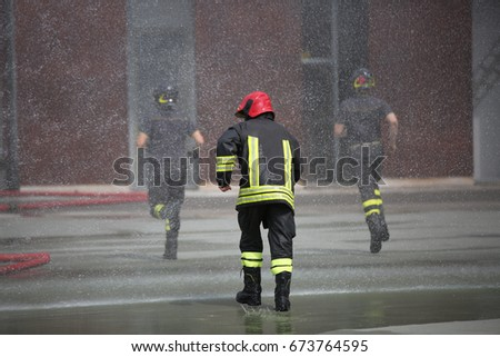 Firefighters run fast under the splashes of water during fire extinguishing
