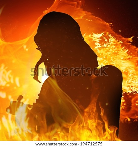 Firefighters silhouette in a burning flame  - stock photo