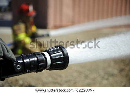 Firefighters spray water during a training exercise. - stock photo