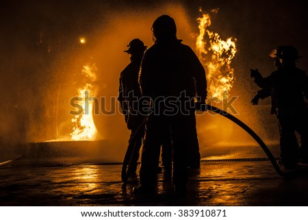 Firefighters standing in a line fighting a fire - stock photo