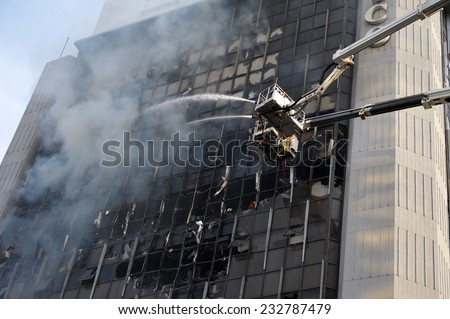 Firefighters Tackle a Blaze in a High Rise Building in Bangkok - stock photo